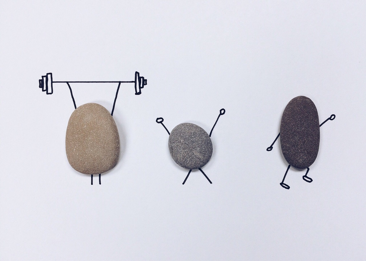 three flat stones lying on a piece of paper with arms and legs drawn around them in black ink. the first is holding up a barbell, the second is doing a jumping jack, and the third is running or doing aerobics